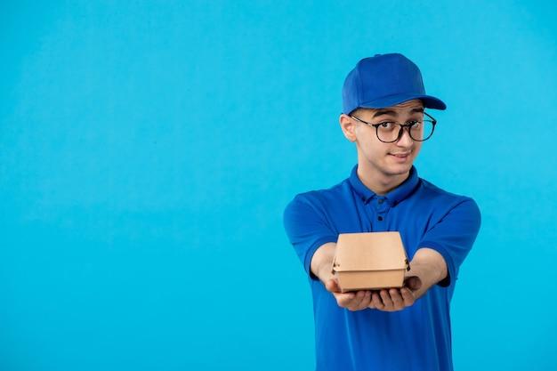 파란색에 작은 음식 패키지와 파란색 유니폼에 남성 택배의 전면보기