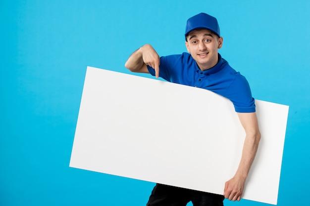 Вид спереди курьера-мужчины в униформе, держащего белый простой стол на синем
