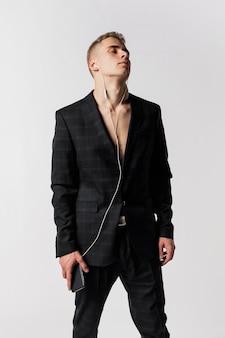 ヘッドフォンで音楽を楽しんでいるスーツの男性ダンサーの正面図