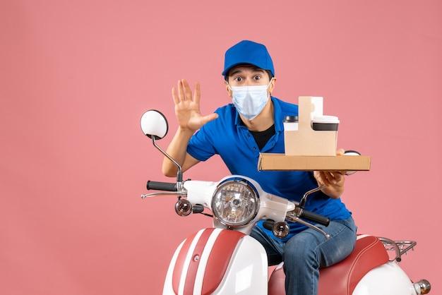 パステル カラーの桃の背景に 10 を示す注文を配達するスクーターに座っている帽子をかぶったマスクの男性配達員の正面図