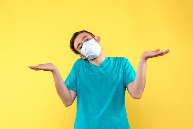 黄色の壁の滅菌マスクで混乱している男性医師の正面図