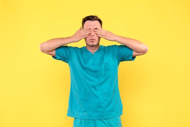 노란색 벽에 그의 눈을 덮고 남성 의사의 전면보기