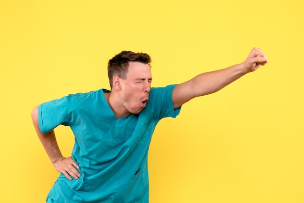 黄色い壁に感情的に喜んでいる男性医師の正面図