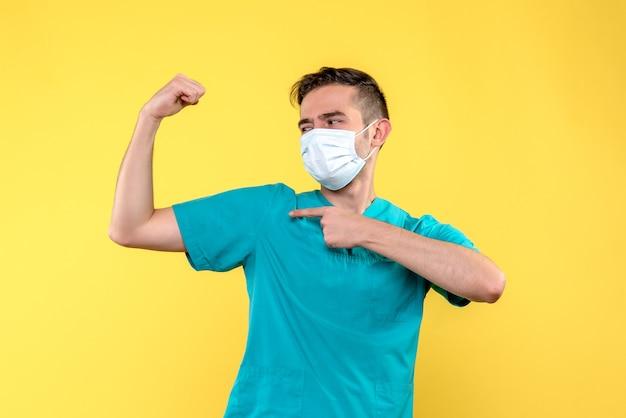 Вид спереди мужского врача, сгибающегося на желтой стене