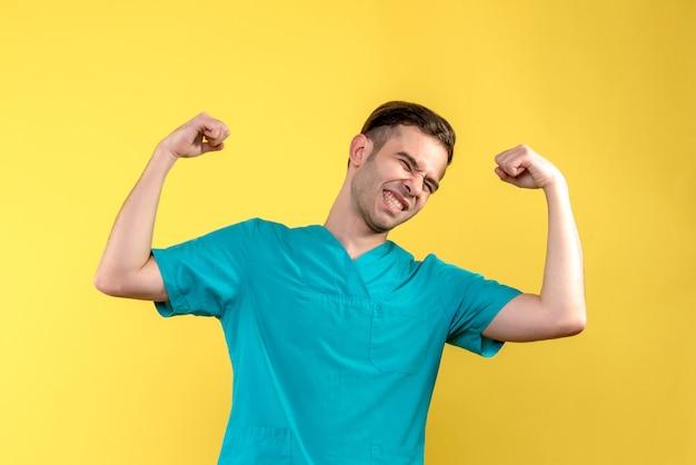 노란색 벽에 flexing 남성 의사의 전면보기