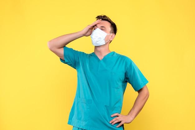 黄色の壁に頭痛を持っている男性医師の正面図