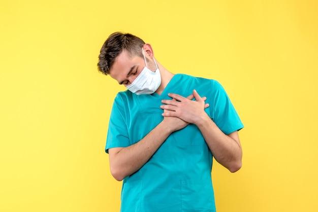 Вид спереди мужчины-врача с болью в сердце на желтой стене