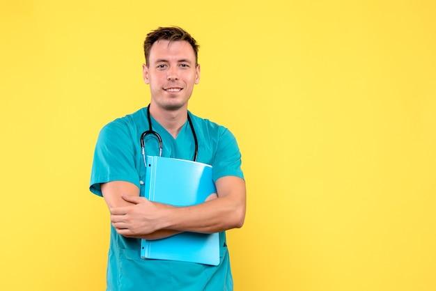 Вид спереди мужского врача, держащего анализы на желтой стене