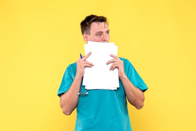 黄色の壁にファイルを保持している男性医師の正面図