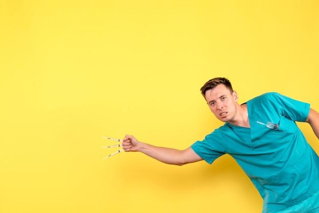 黄色の壁に注射を保持している男性医師の正面図