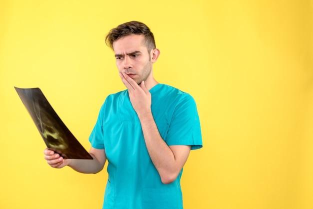 노란색 벽에 엑스레이 들고 남성 의사의 전면보기