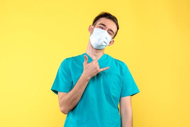 노란색 벽에 마스크에 남성 의사의 전면보기