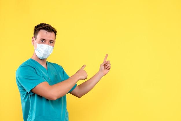 薄黄色の壁にマスクで男性医師の正面図