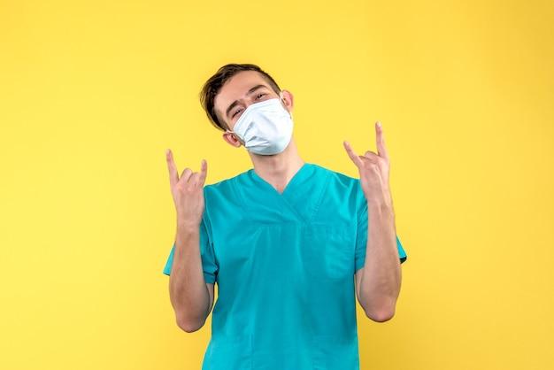 黄色い床のウイルス健康covidmedicのマスクの男性医師の正面図