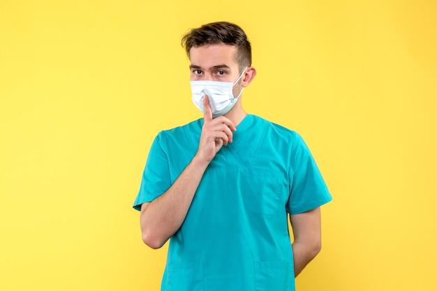黄色の壁にマスクで男性医師の正面図