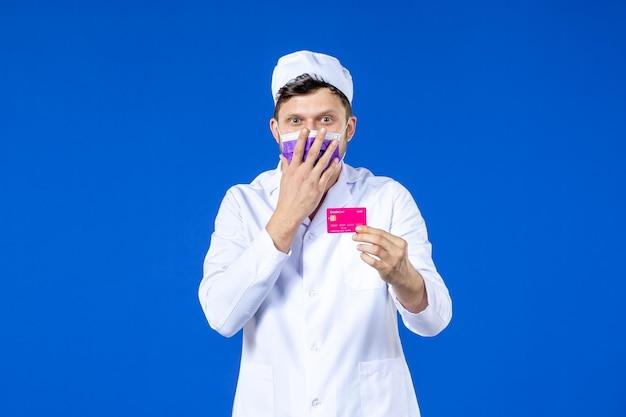 青のクレジットカードを保持している医療スーツとマスクの男性医師の正面図