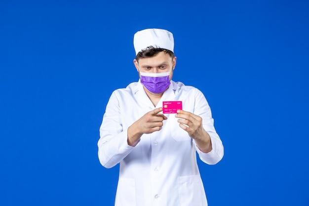 Вид спереди мужчины-врача в медицинском костюме и маске, держащего кредитную карту на синем