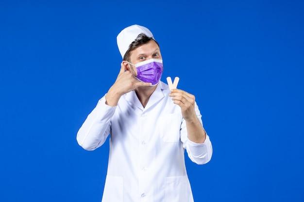 파란색에 작은 의료 패치를 들고 의료 양복과 마스크 남성 의사의 전면보기