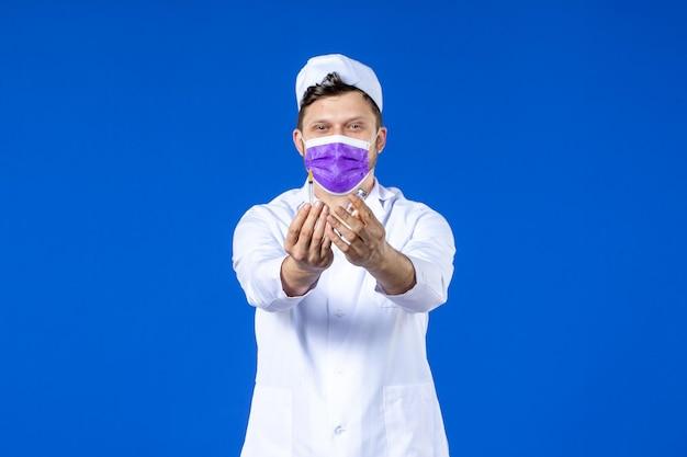 Вид спереди мужчины-врача в медицинском костюме и маске, держащего вакцину и инъекцию на синем