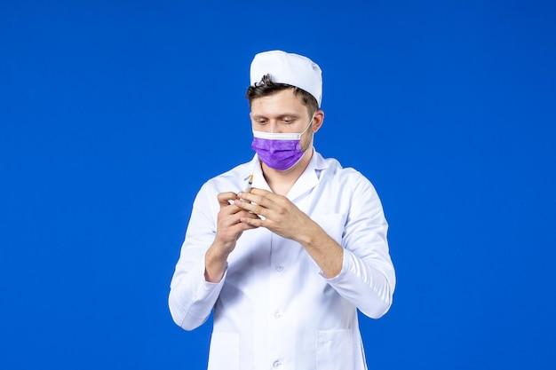 青の注射とワクチンで医療スーツとマスクの男性医師の正面図
