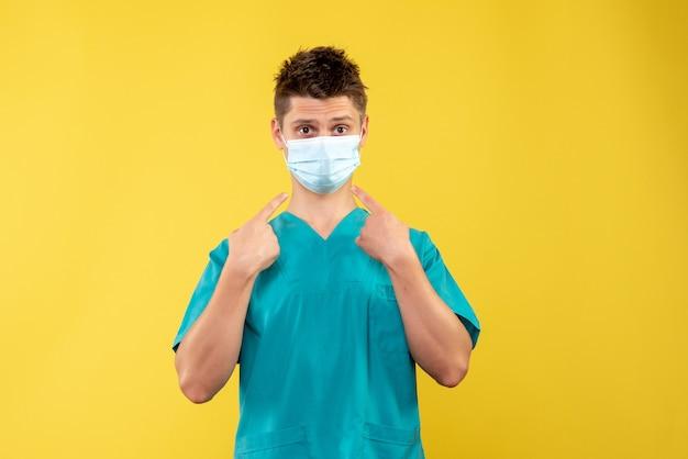 노란색 벽에 의료 소송 및 보호 마스크에 남성 의사의 전면보기