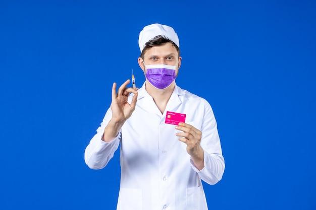医療スーツと青の注射とクレジットカードを保持している紫色のマスクの男性医師の正面図