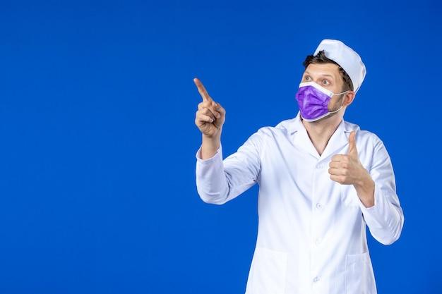 Вид спереди мужского врача в медицинском костюме и фиолетовой маске на синем