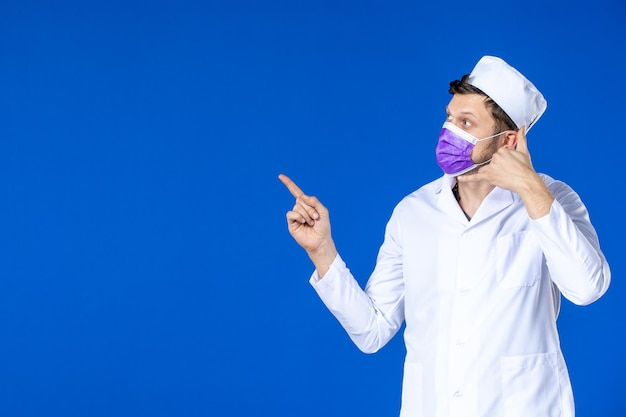 파란색에 의료 양복과 보라색 마스크 남성 의사의 전면보기