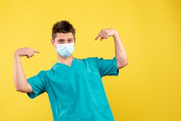 Вид спереди мужского врача в медицинском костюме и стерильной маске на желтой стене
