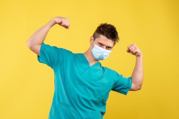 医療スーツと黄色の壁に滅菌マスクの男性医師の正面図