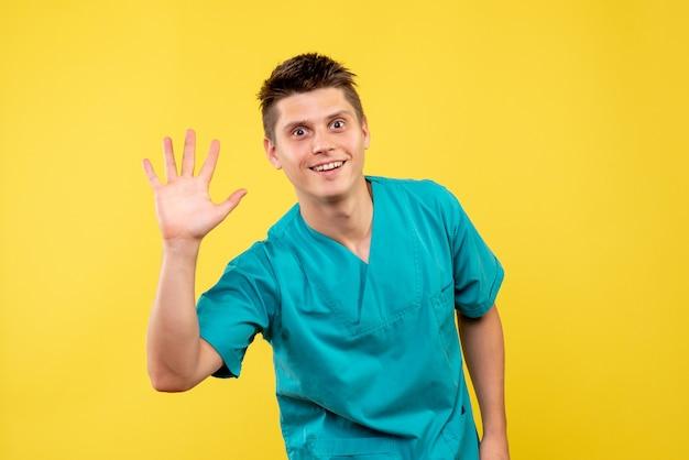 黄色の壁に挨拶する医療スーツの男性医師の正面図