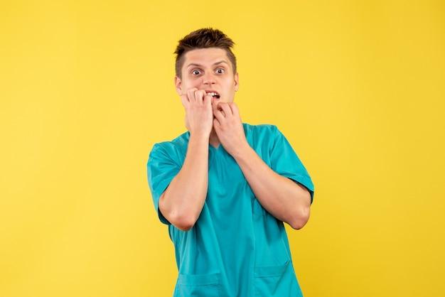 黄色の壁に医療スーツを着た男性医師の正面図