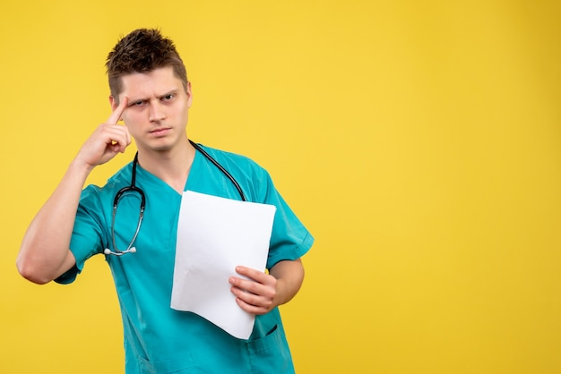Вид спереди мужского врача в медицинском костюме с анализом на желтой стене
