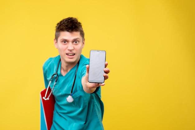 Вид спереди мужского врача в медицинском костюме с телефоном и заметкой на желтой стене