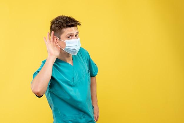 노란색 벽에 듣고 멸균 마스크와 의료 소송에서 남성 의사의 전면보기