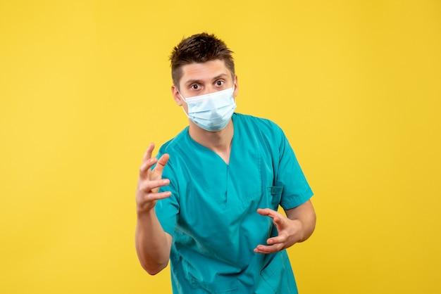 Вид спереди мужчины-врача в защитной маске на желтой стене