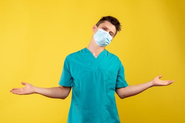 黄色の壁の保護マスクで男性医師の正面図