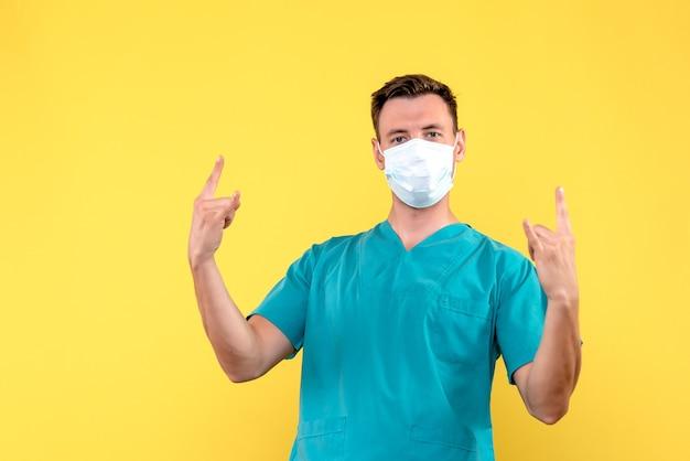 Вид спереди мужского врача в стерильной маске на желтой стене