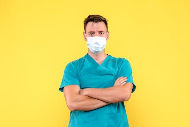 黄色い壁のマスクに立っているだけの男性医師の正面図