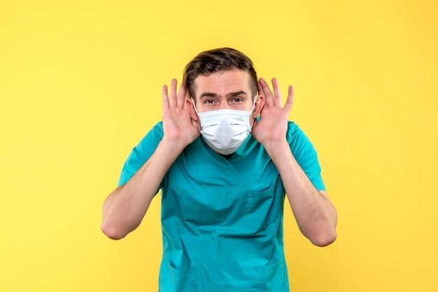 Вид спереди мужского доктора, слушающего на желтой стене