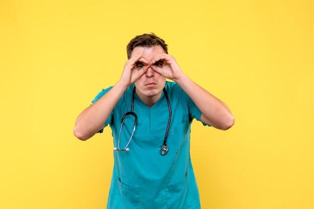노란색 벽에 그의 손가락을 통해 찾고 남성 의사의 전면보기