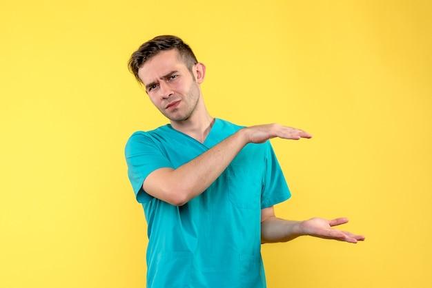 노란색 벽에 크기를 보여주는 남성 의사의 전면보기