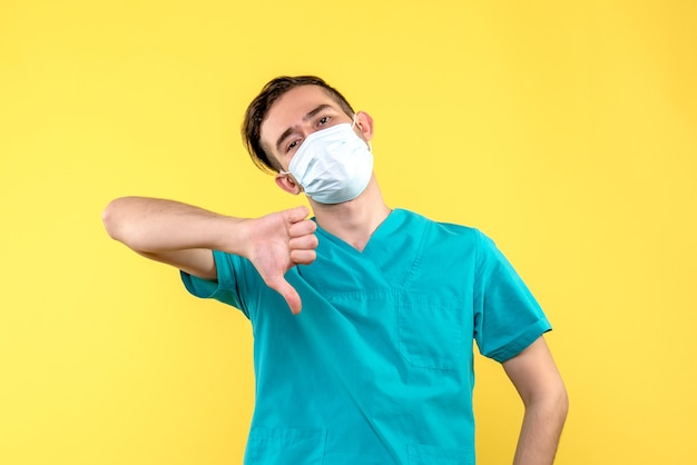 黄色の壁に異なるサインを示す男性医師の正面図