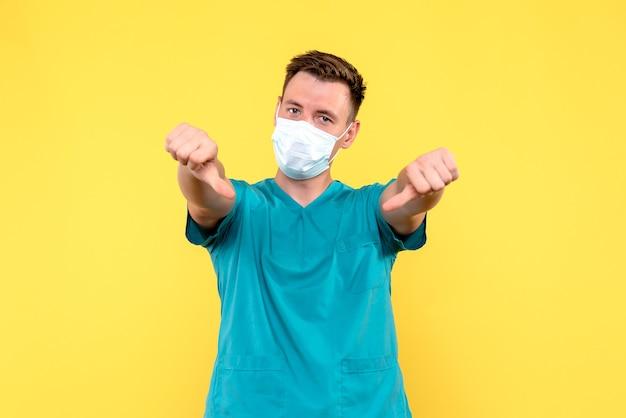 黄色の壁に異なる兆候を示す男性医師の正面図
