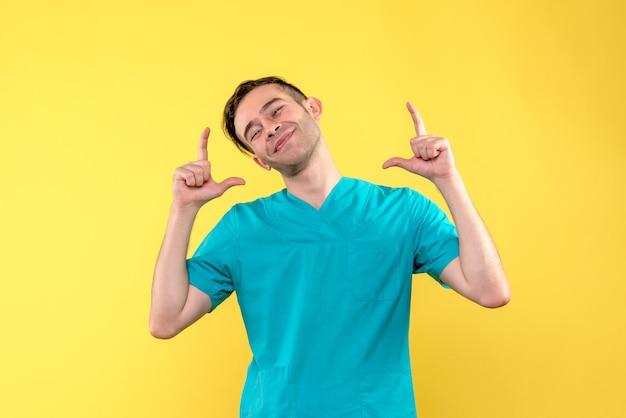 Вид спереди мужчины-врача, улыбаясь на желтой стене