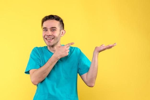 黄色の壁に笑みを浮かべて男性医師の正面図