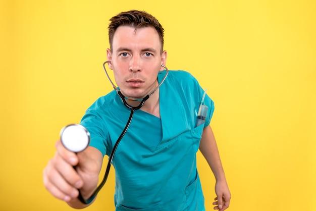 黄色の壁に眼圧計を使用して男性医師の正面図