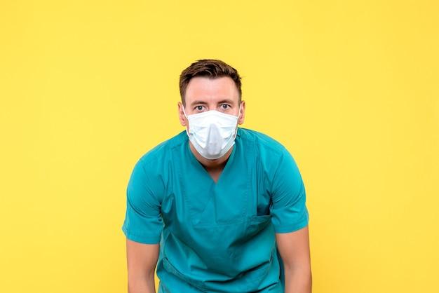 노란색 벽에 마스크를 쓰고 남성 의사의 전면보기