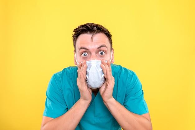 노란색 벽에 멸균 마스크를 쓰고 남성 의사의 전면보기