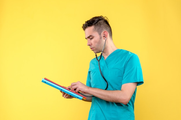 黄色の壁に分析と聴診器を備えた男性医師の正面図